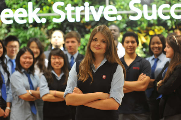 A group of students with their arms cross standing in front of a lit sign that says 'Seek. Strive. Success.'