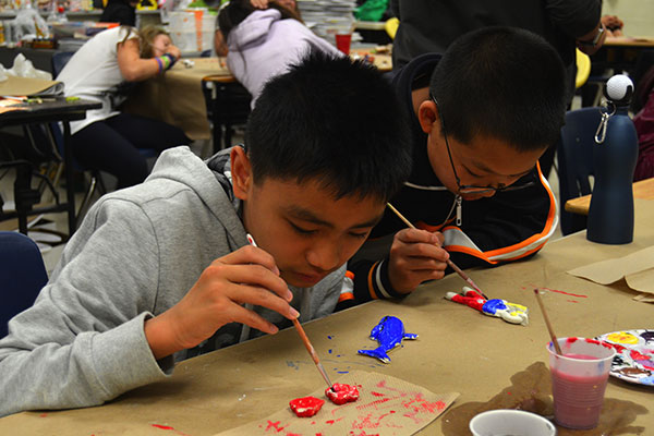 2 students painting crafts