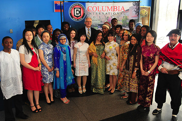 A large and diverse group of students and staff wearing their culture's traditional clothing