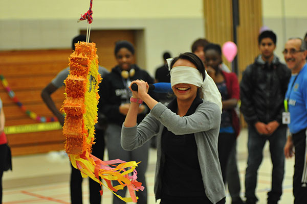 A student blindfolded and about to strike a piñata