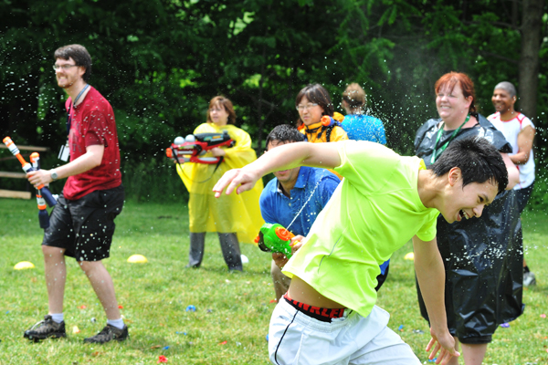 A group of students outside having a watergun fight.