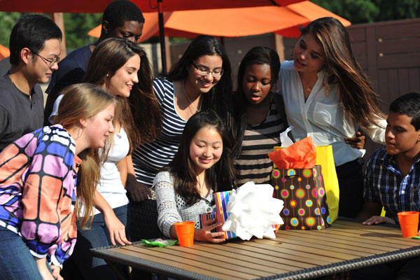 A group of students gathered watching another student open presents