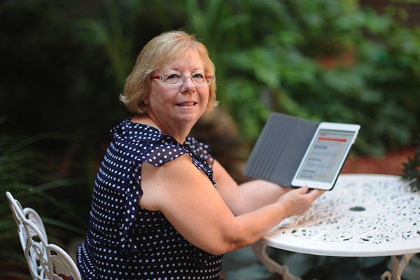 The parent of a student checking grades from their tablet in their backyard.