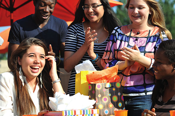 A group of students clapping for a another student, who is in front of a number of presents