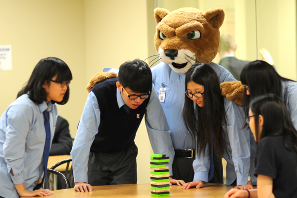 A group of students playing Jenga, being encouraged by the school's mascot, Cicero the cougar